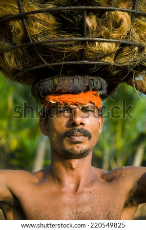 Indigenous manual labor worker carrying on the head. - stock photo
