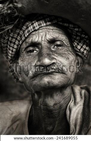 Indigenous senior Indian man looking grumpy at the camera. - stock photo