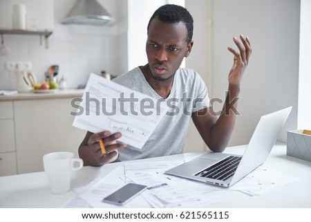 Indignant angry irritated african american male sitting at kitchen table, looking at papers in shock, astonished with amount of unpaid bills. Financial stress, feeling depressed and frustrated