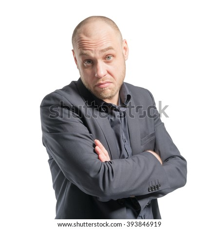 Indignant bald man in a gray suit with arms crossed. Isolated