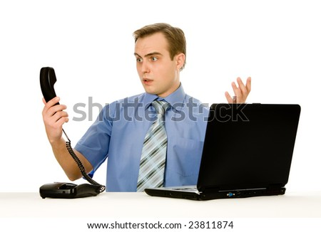 Indignant young businessman working on a laptop. Isolated on white. - stock photo