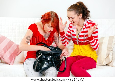 Indignant young girl sitting on sofa and looking on searching something in handbag girlfriend - stock photo