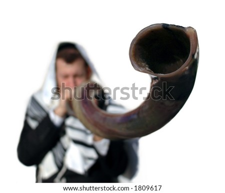 indistinct man in background blur blows a long yemenite shofar horn with focus on the open end of the horn; isolation on white - stock photo