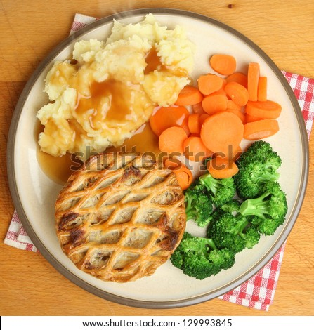 Individual chicken pie with mash, vegetables and gravy. - stock photo