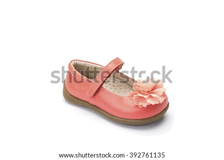 Individual childs peach pink coloured dress shoe with a pretty flower on the toe shot at a 3/4 angle on a white background