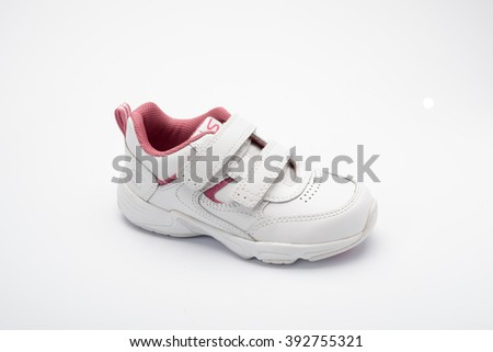 Individual childs white trainer or sneaker or running shoe with pink inside shot at a 3/4 angle on a white background