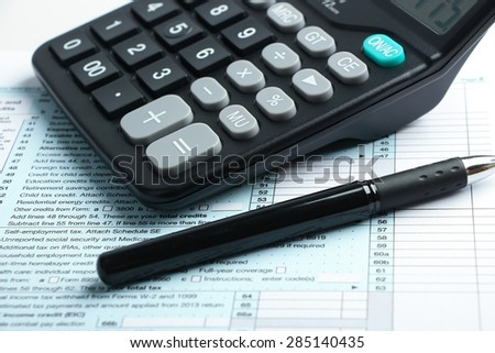 Individual income tax return form, pen and calculator is on the desk. - stock photo