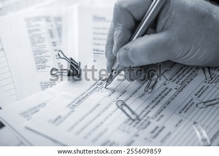 Individual preparing their income tax report in black and white - stock photo