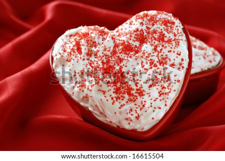 Individual sized, heart-shaped cakes with white frosting nestled in the soft folds of a red tablecloth. Shallow dof. - stock photo