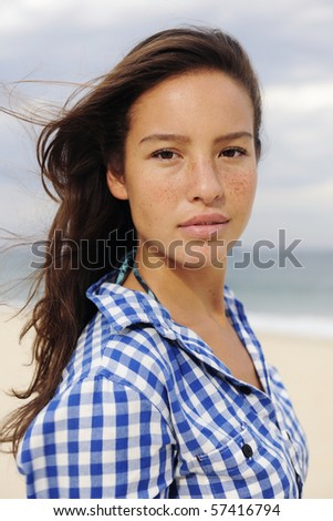 individuality: portrait of a beautiful young woman at the sea - stock photo