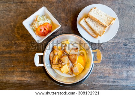 Indochina pan-fried egg with pork and toppings, Breakfast food in Thai style On Wood Table - stock photo