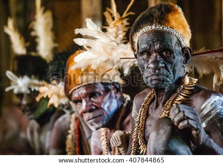 INDONESIA, IRIAN JAYA, ASMAT PROVINCE, JOW VILLAGE - JUNE 12: Men Asmat tribe are sitting at home. On June 12, 2012  Jow Village, Asmat province, Indonesia - stock photo