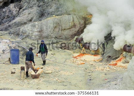 Indonesia, Java Island, February, 2010. Men work at production of sulfur in a crater of an active volcano of Kawa Ijen - stock photo