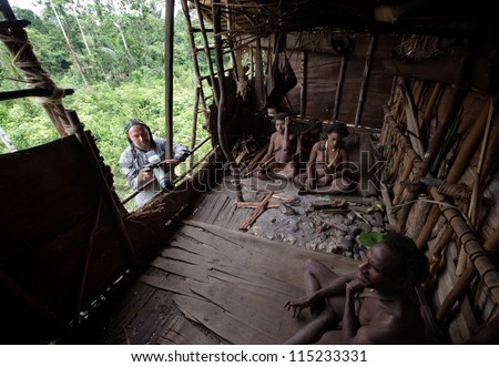 INDONESIA, NEW GUINEA, IRIAN JAYA,  ONNI VILLAGE - JUNE 27:  White man with camera and Korowai people in the traditional wooden house built on a tree. New Guinea Island, Indonesia. June 27 2009 - stock photo
