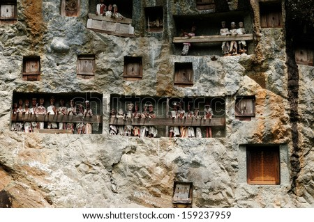 Indonesia, Tana Toraja - Londa, is a  burial cave at the base of a massive cliff face.The entrance to the cave is guarded by a balcony of tau tau. Inside the cave is a colection of coffins - stock photo