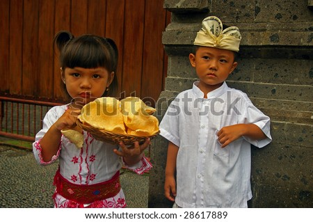Indonesian children, wearing traditional Balinese clothes carrying Prawn crackers, Jimbaran, Bali, Indonesia.