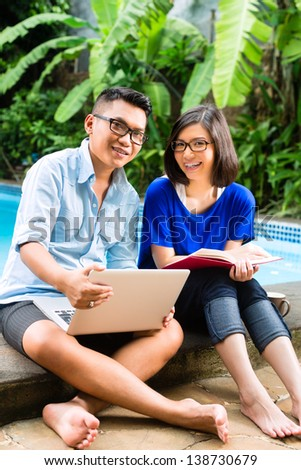 Indonesian couple in a tropical environment, he is working she is reading a book - stock photo