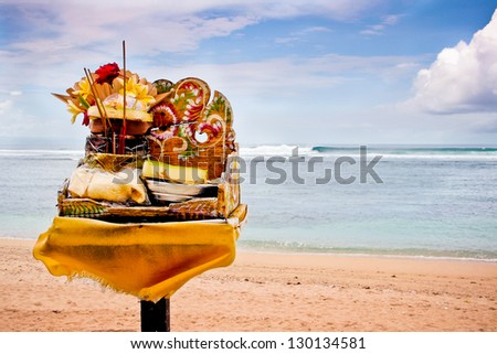 indonesian daily offering to the gods with beach background - stock photo