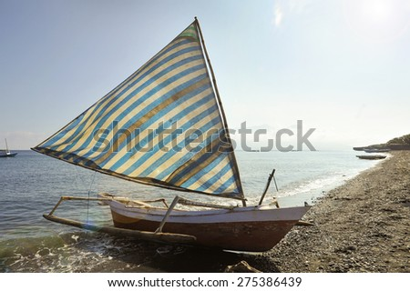 Indonesian Fishing Boat. An Indonesian fishing boat, called a jukung, returns after a days work landing on the island of Wera in the Indonesian archipelago. - stock photo