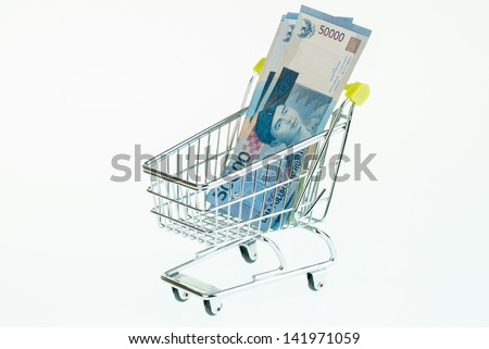 Indonesian rupiah in shopping cart over white background  - stock photo