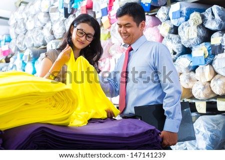 Indonesian textile workers choosing some colorful fabrics in a asian storehouse
