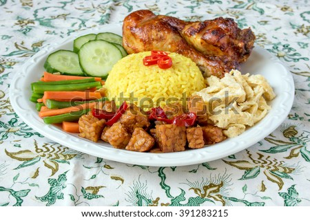 Indonesian traditional food, nasi kuning / yellow turmeric rice served with roasted chicken drumstick, vegetables, chooped omelet and tempeh with batik background - stock photo