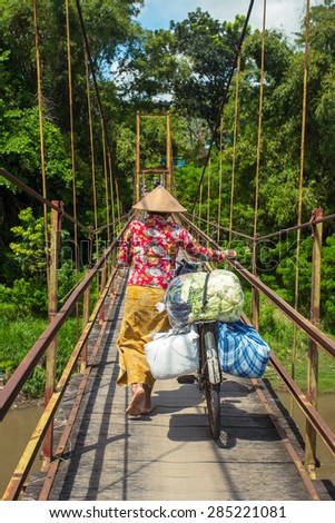Indonesian woman in traditional hat carrying bags on her bicycle across the bridge - stock photo