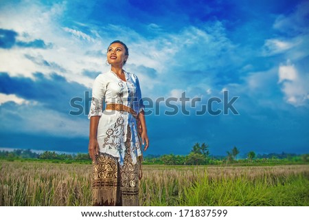 indonesian woman posing on a field - stock photo