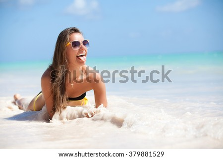 Indoor bright fashion summer portrait of beach vacation woman relaxing on sand happy, showing her tongue. Model looking happy lying down on perfect white sand beach and turquoise ocean water.