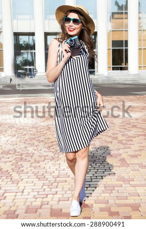 Indoor bright fashion summer portrait of stylish cheeky hipster woman, showing her tongue, have long brunette hairs perfect tanned fit slim body, wear sneakers  and bikini pants and young sunglasses. - stock photo