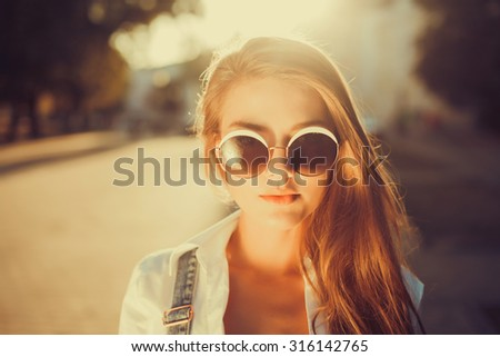 Indoor bright fashion summer portrait of stylish cheeky hipster woman, showing her tongue, have long brunette hairs perfect tanned fit slim body,sneakers bikini pants and young sunglasses.  - stock photo