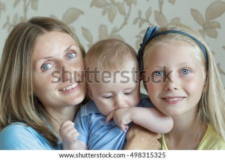 Indoor family portrait of happy mother with two adorable siblings