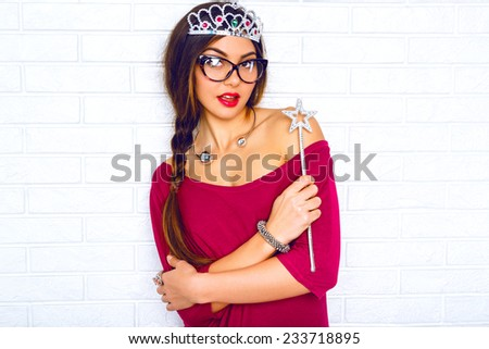 Indoor fashion lifestyle positive portrait of young sexy brunette hipster woman, ready for masquerade party wearing  fairy costume funny fake crown and magic wand.Bright colors, brick wall background. - stock photo