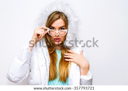 Indoor fashion portrait of pretty blonde woman with long hairs and natural make up, poring against white wall in winter warn jacket and cute mint sweater, vintage glasses, joy, winter. - stock photo