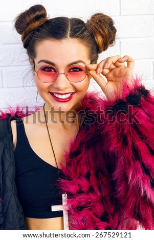 Indoor fashion portrait of stylish young woman smiling and  having fun alone, wearing trendy hot pink fake fur coat and round sunglasses, eighties style. Urban white wall background. - stock photo