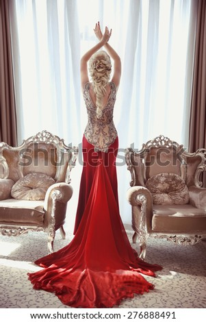 Indoor full length portrait of elegant blond woman in red gown with long train of dress posing between two modern armchairs in front of window at interior.  - stock photo