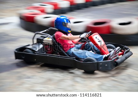 Indoor karting race (rushing kart and safety barriers) - stock photo
