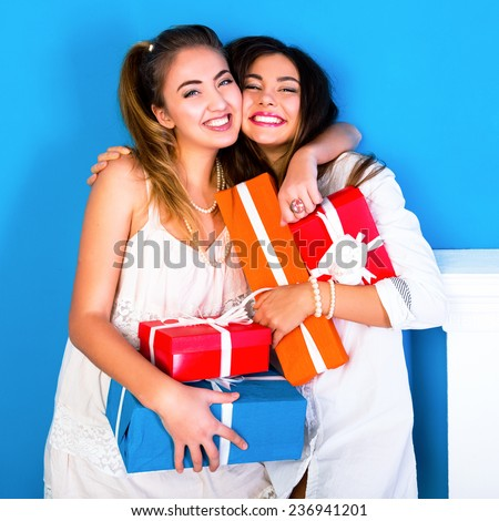 Indoor lifestyle portrait of two pretty young funny girls friends hugs smiling and having fun, holding bright holiday presents, ready for celebration. Wearing cozy pajamas. - stock photo