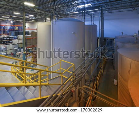 Indoor liquid storage tanks in a manufacturing facility - stock photo