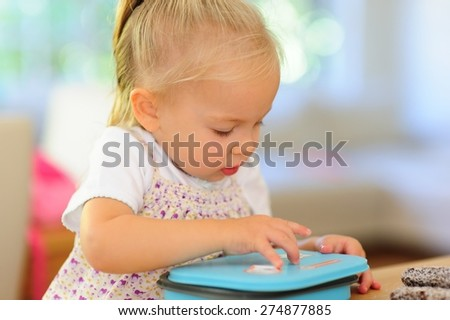 Indoor portrait of a cute little child, adorable baby or toddler girl opening a lunch box with yummy treats in it at home