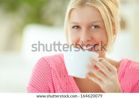 Indoor portrait of a smiling Caucasian woman drinking tea.