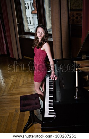 indoor portrait of a young female piano player - stock photo