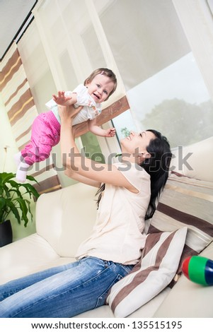 indoor portrait of a young woman with toddler twins in the living room