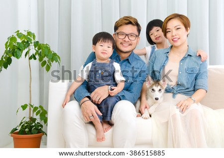 Indoor portrait of asian family and their puppy in the living room - stock photo