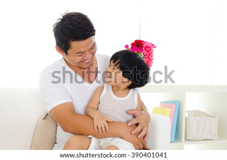 Indoor portrait of asian father and son  - stock photo