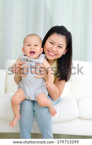 Indoor portrait of asian mother and her cheerful baby - stock photo