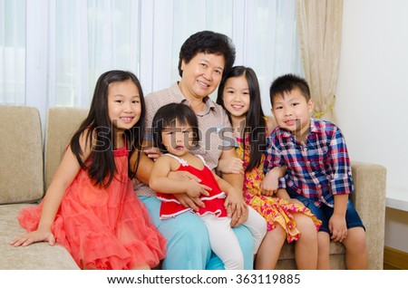 Indoor portrait of asian senior woman and her lovely grandchildren - stock photo