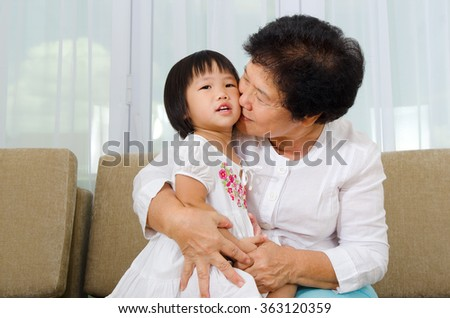 Indoor portrait of asian senior woman kiss her granddaughter - stock photo
