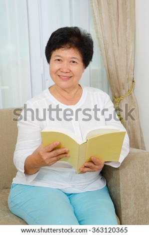 Indoor portrait of asian senior woman reading book - stock photo