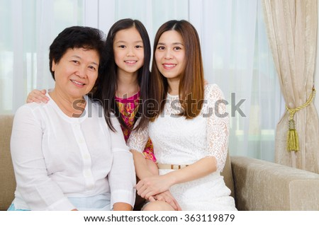Indoor portrait of asian senior woman together with daughter and grandchild - stock photo